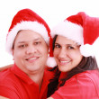 Stock Photo: Young happy couple near with Santa hats. Isolated over white bac