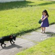 Foto Stock: Little girl having trouble with her dog in park