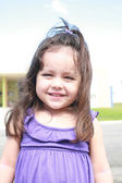Cute little girl smiling in a park close-up — Stock Photo