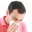 Young man with a cold blowing nose on tissue — Stock Photo #8615162