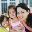 Stock Photo: Mother and Daughters portrait outdoors in front of their home