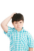 Boy scratches his head in puzzlement or confusion, as if ponderi — Stock Photo