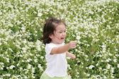 Baby girl happy in a garden of flowers — Stock Photo