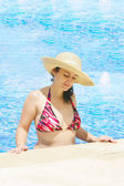 The beautiful woman in a hat in pool — Stock Photo