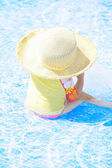 Fashion toddler girl playing in swimming pool — Stock Photo