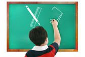 Boy in classroom thinking, writing and counting on board — Stock Photo