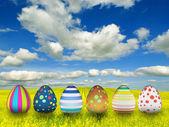 Muchos huevos de pascua de color sobre fondo de cielo azul — Foto de Stock