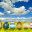 Many color easter eggs over blue sky background — ストック写真
