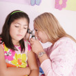 Doctor examining little girl's ears with the otoscope — Stock Photo