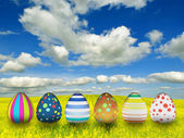 Many color easter eggs over blue sky background — Stock Photo