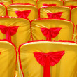 Stock Photo: Rows of seats with golden yellow cover and red tape