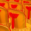 Foto Stock: Rows of seats with golden yellow cover and red tape