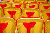 Rows of seats with a golden yellow cover and red tape — Stock Photo