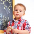 Stock Photo: Little boy draws on the board