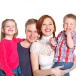 Happy family smiling at the camera — Stock Photo
