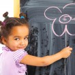 Постер, плакат: Little mulatto girl draws on the board