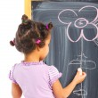 Little mulatto girl draws on the board — 图库照片
