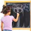 Little mulatto girl draws on the board — Stock Photo