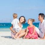 Family of four on tropical beach — Stock Photo