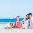 Family of four on tropical beach — Stock Photo #10645744