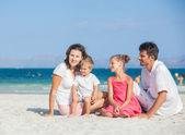 Familie van de vier op tropisch strand — Stockfoto