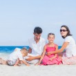 Family of four on tropical beach — Stock Photo #10715533