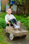 Cute boy plays with toy tools in the garden. — Stock Photo