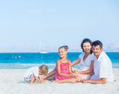 Family of four on tropical beach — Stock Photo