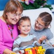 Grandmother and her two grandchildren with gifts — Stock Photo #8189110
