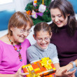 Girl and her mother and grandmother with gifts — Stock Photo