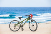 Bicycle with helmet, stand on the beach. — Stock Photo