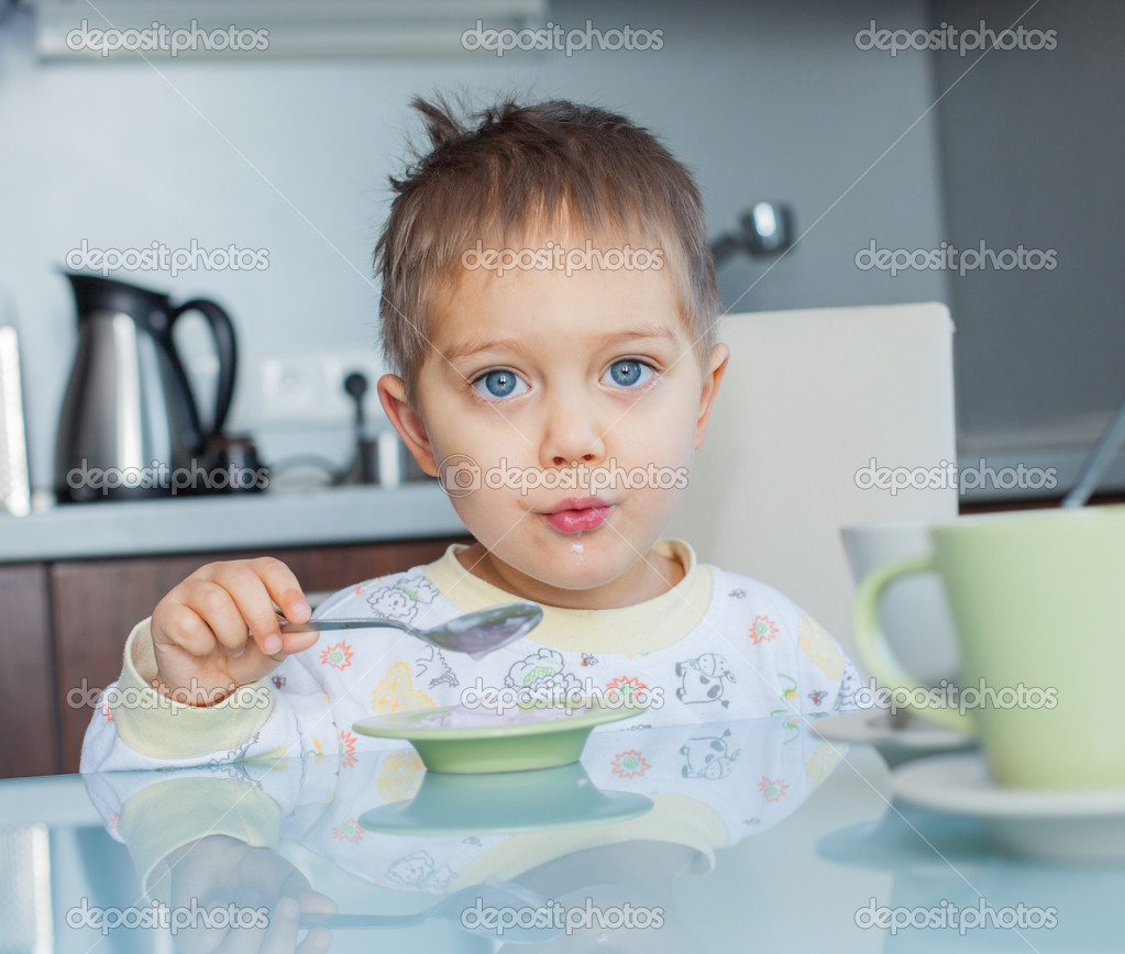 Happy little cute boy in pajamas eating breakfast at a table in the kitchen  Stock Photo #8934867