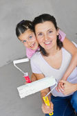 Happy Mother and douther painting a wall — Stock Photo