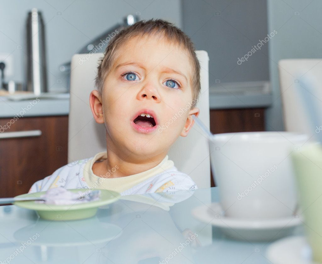 Happy little cute boy in pajamas eating breakfast at a table in the kitchen — Stock Photo #8958528