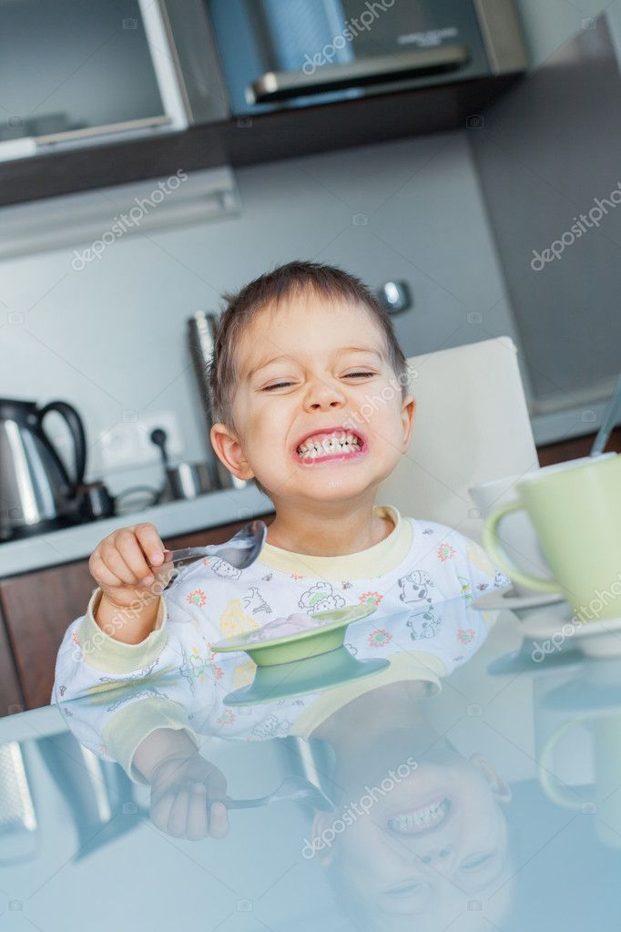 Happy little cute boy in pajamas eating breakfast at a table in the kitchen. Vertical view — Stock Photo #8958584
