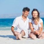 Family sitting on tropical beach — Stock Photo