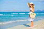 Adorable girl wearing elegant hat on the beach — Stock Photo