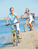 Cute girl with her mother and brother ride bikes — Stock Photo