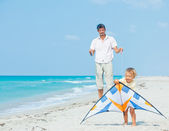 Boy with father on beach playing with a kite — Stock Photo