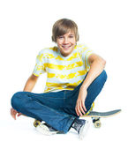 Blond boy on sitting on skateboard — Stock Photo
