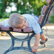 Cute little boy relaxing on bench in city — Stock Photo #9058645
