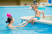 Boy with mather playing in a pool of water — Stock Photo