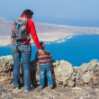 Back view mother and son standing on cliff's edge — Stock Photo