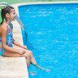 Stock Photo: Pretty young girl at pool's edge
