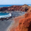 Exotic beach with black sand — Stock Photo