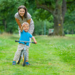 Stock Photo: Little boy on bicycle and his mother