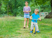 Little boy on a bicycle and his sister — Stock Photo
