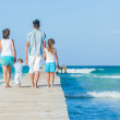 Family of four on wooden jetty by the ocean — Stock Photo