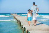 Family of three on jetty by the ocean — Stock Photo
