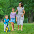 Little boy on a bicycle and his mother and sister — Stock Photo #9239915